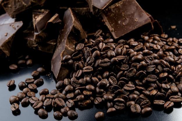 Chocolate orgânico escuro e grãos de café no fundo de concreto.