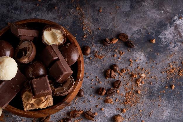 Chocolate preto e branco quebrado em uma tigela de madeira. pedaços de chocolates em uma mesa de pedra cinza