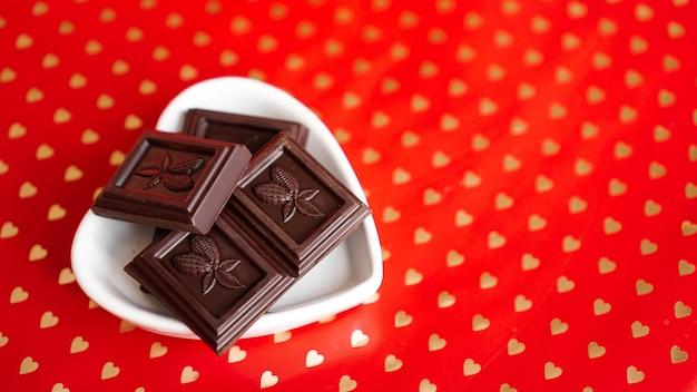 Chocolate preto em um prato em forma de coração no vermelho