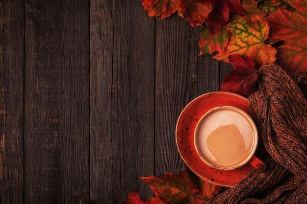 Chocolate quente, cachecol de malha e folhas multicoloridas.
