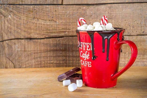 Chocolate quente caseiro em caneca vermelha, com mini marshmallows e gotas de chocolate, decoração de bengala, espaço de cópia