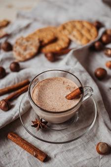 Chocolate quente com biscoitos, paus de canela, anis, nozes na mesa de madeira.