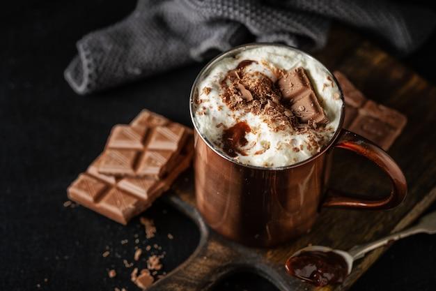 Chocolate quente com chantilly e chocolate ralado em uma xícara. fechar-se