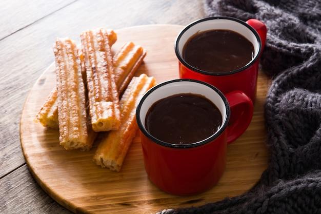 Chocolate quente com churros na mesa de madeira.