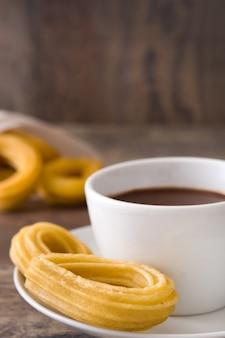 Chocolate quente com churros na mesa de madeira