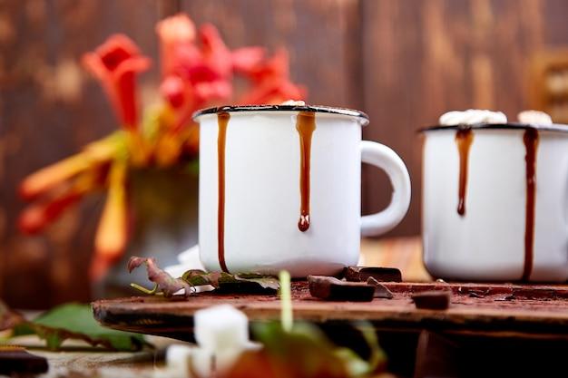 Chocolate quente com doces de marshmallow em fundo de madeira.