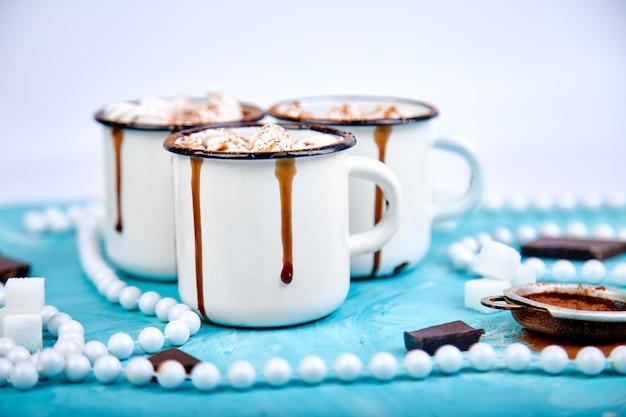 Chocolate quente com doces de marshmallow na madeira.