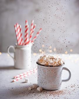 Chocolate quente com marshmallow, cacau espalhado e um tubo de papel vermelho em uma mesa cinza