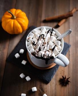 Chocolate quente com marshmallow e canela em uma caneca branca sobre uma mesa de madeira. vista do topo