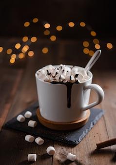 Chocolate quente com marshmallow e canela em uma caneca branca sobre uma mesa de madeira