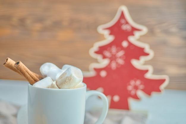 Chocolate quente com marshmallows com canela no fundo vermelho