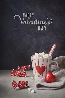 Chocolate quente com marshmallows, copo branco com coração em cima da mesa, texto de saudação