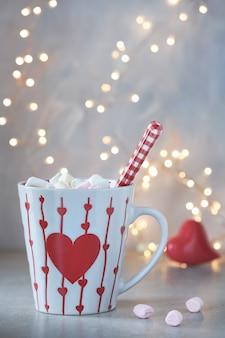 Chocolate quente com marshmallows, coração vermelho na xícara, fundo de inverno com luzes fora de foco