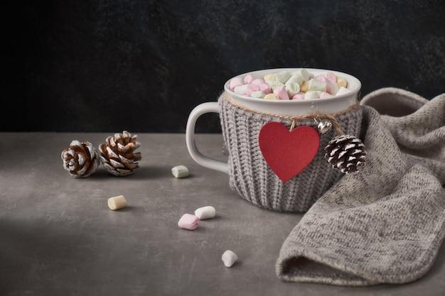 Chocolate quente com marshmallows, coração vermelho no copo em cima da mesa com decorações de inverno. aniversário ou dia dos namorados.
