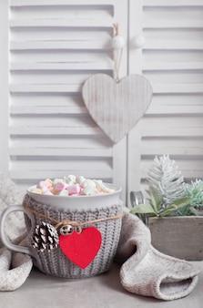 Chocolate quente com marshmallows, coração vermelho no copo em cima da mesa com decorações de inverno