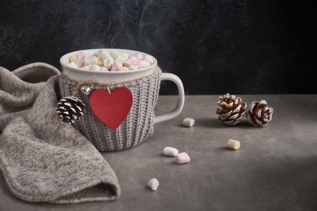 Chocolate quente com marshmallows, coração vermelho no copo em cima da mesa