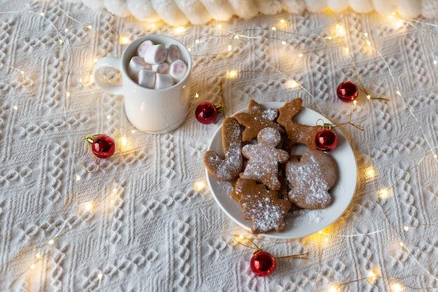 Chocolate quente com marshmallows e biscoitos de gengibre, guirlanda de luz festiva e brinquedos de árvore de natal vermelhos em uma cama branca