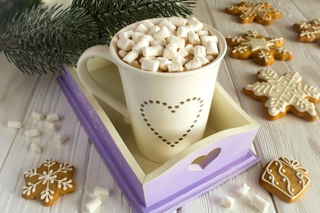 Chocolate quente com marshmallows e composição de natal em fundo branco de madeira