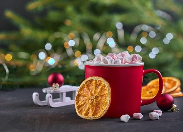 Chocolate quente com marshmallows e laranja cristalizada seca em copos vermelhos para o natal. conceito de férias. foco seletivo.