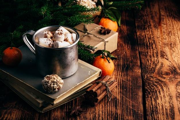 Chocolate quente com marshmallows e pão de gengibre sobre livros antigos