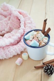 Chocolate quente com marshmallows e paus de canela. cor pastel