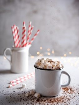 Chocolate quente com marshmallows e um tubo de papel vermelho em uma mesa cinza