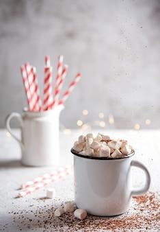 Chocolate quente com marshmallows e um tubo de papel vermelho sobre uma mesa cinza. foto de natal. visão frontal e macro