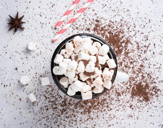 Chocolate quente com marshmallows e um tubo de papel vermelho sobre uma mesa cinza. foto de natal. vista de cima e macro