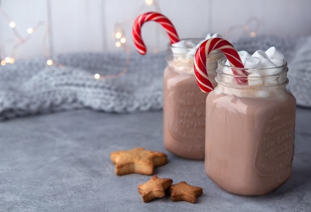 Chocolate quente com marshmallows e uma cana de açúcar em canecas de vidro sobre um fundo cinza com um cachecol e luzes