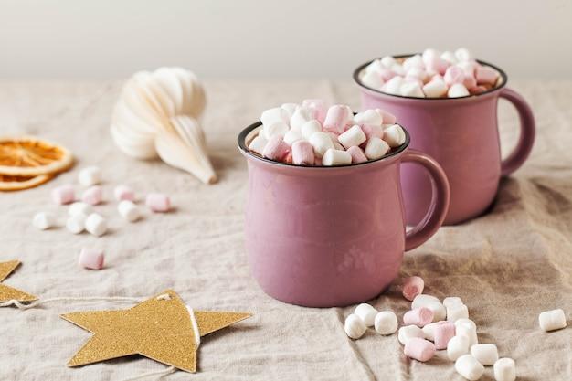 Chocolate quente com marshmallows em canecas em uma toalha de mesa de linho com brinquedo de natal