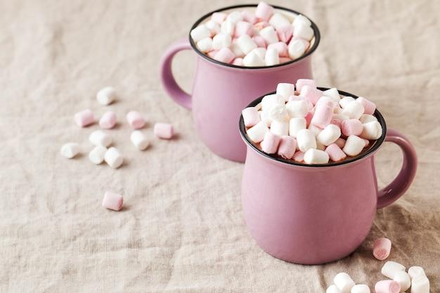 Chocolate quente com marshmallows em canecas em uma toalha de mesa de linho estilo retrô