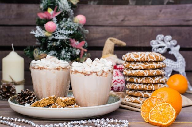 Chocolate quente com marshmallows em copos e biscoitos de natal em decorações de natal