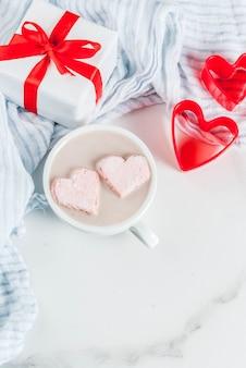 Chocolate quente com marshmallows em forma de coração, celebração do dia dos namorados, com cortadores de biscoito vermelho e copyspace de caixa de presente dos namorados vista superior