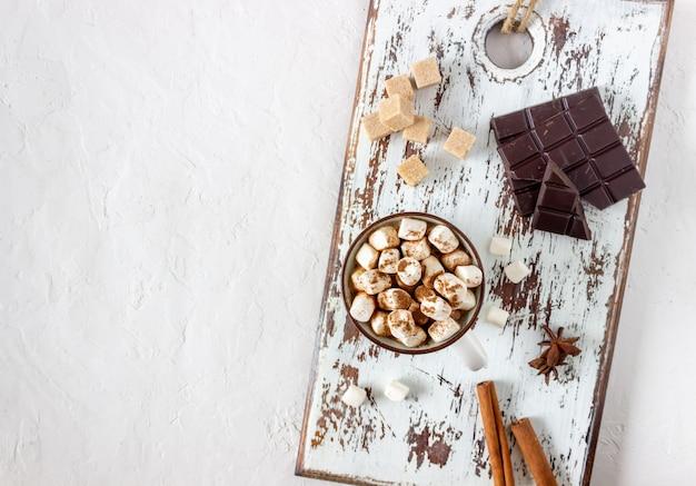 Chocolate quente com marshmallows em uma caneca branca sobre um fundo branco. receitas.