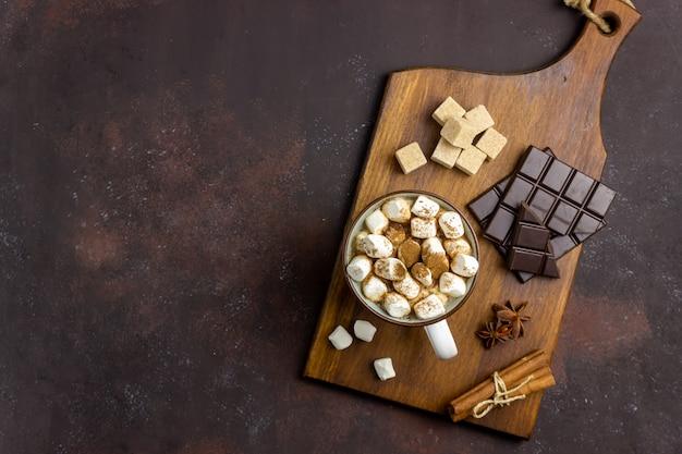 Chocolate quente com marshmallows em uma caneca branca sobre um fundo enferrujado. inverno. receitas.