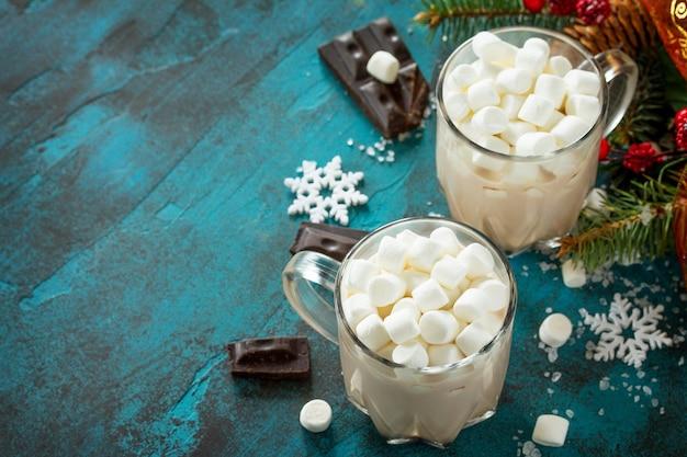 Chocolate quente com marshmallows em uma pedra azul ou mesa de concreto copie o espaço