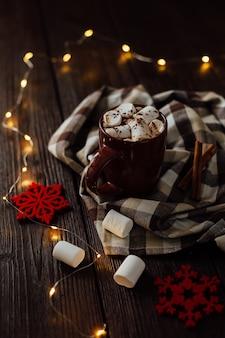 Chocolate quente com marshmallows em uma xícara de cerâmica na mesa de madeira marrom