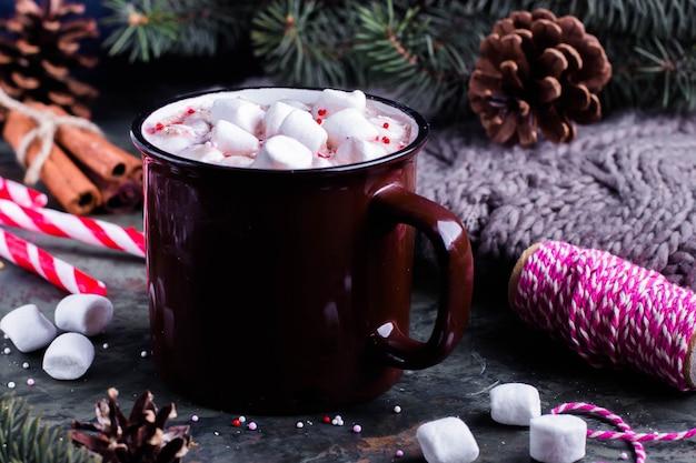 Chocolate quente com marshmallows em uma xícara de cerâmica na mesa. decoração festiva. conceito de natal.