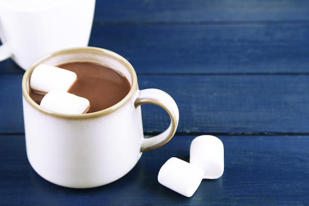 Chocolate quente com marshmallows na caneca, em superfície de madeira