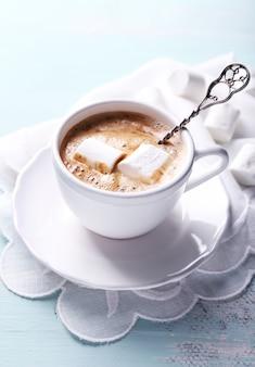 Chocolate quente com marshmallows na caneca, mesa de madeira colorida