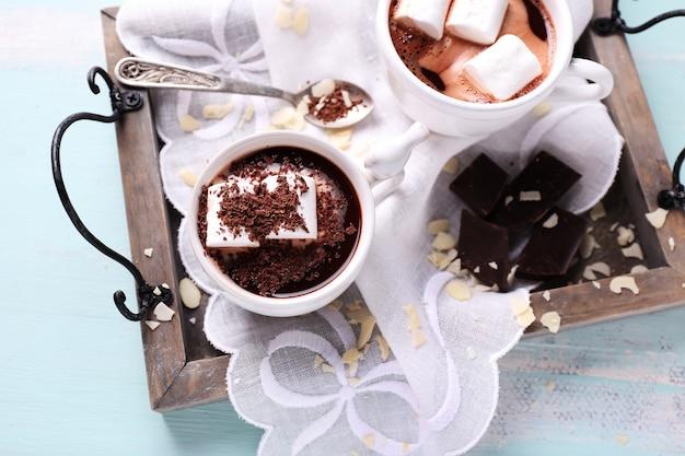Chocolate quente com marshmallows na caneca, na bandeja, na cor de fundo de madeira