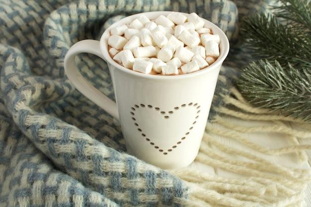 Chocolate quente com marshmallows na manta azul sobre fundo branco de madeira
