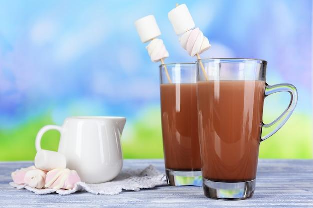 Chocolate quente com marshmallows, na superfície azul