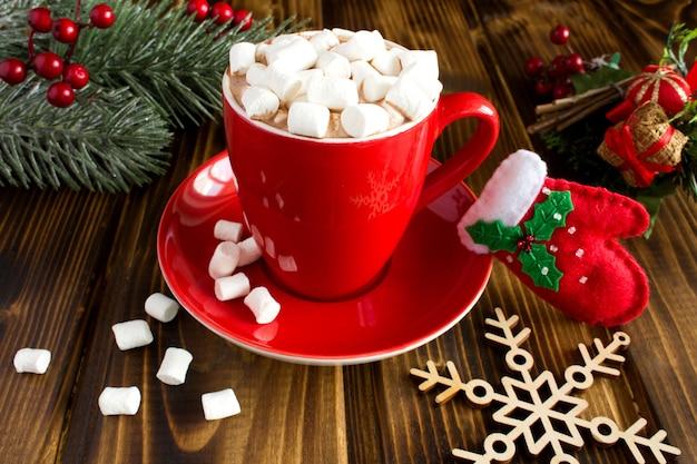 Chocolate quente com marshmallows na xícara vermelha no fundo de madeira marrom