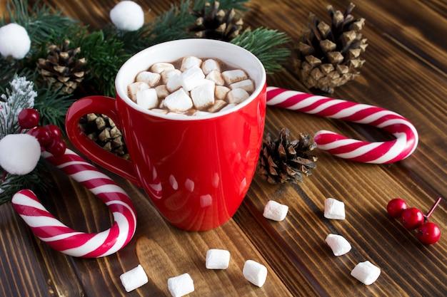 Chocolate quente com marshmallows na xícara vermelha no fundo de madeira