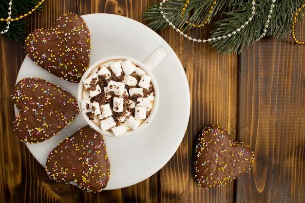 Chocolate quente com marshmallows no copo branco e composição de natal no fundo de madeira marrom. espaço da cópia. vista superior.