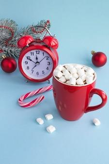 Chocolate quente com marshmallows no copo vermelho, despertador vermelho e composição de natal
