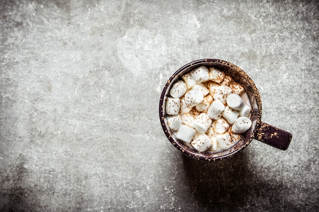 Chocolate quente com marshmallows. sobre um fundo de pedra.