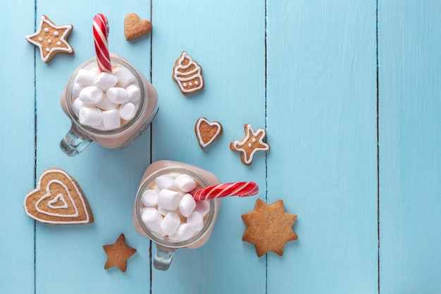 Chocolate quente com marshmallows, uma cana de açúcar e biscoitos de gengibre em um fundo turquesa.
