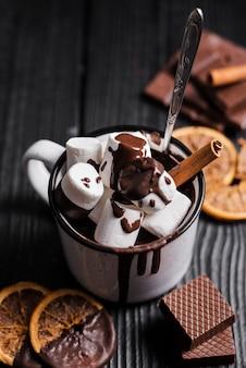 Chocolate quente com pau de marshmallow de canela e fatias de laranja secas